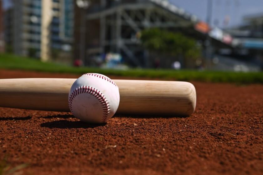 Baseball and bat on a ballfield.