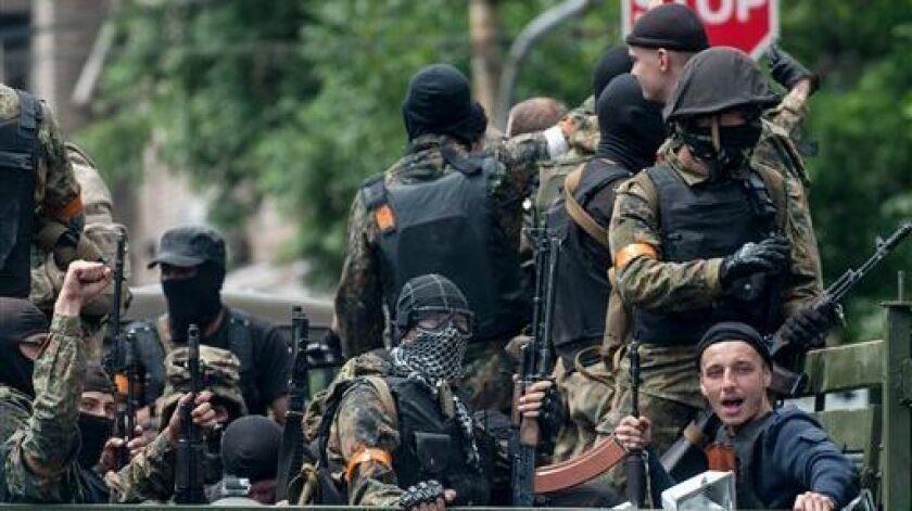 Ukrainian troops leave the site of a battle in Mariupol, eastern Ukraine, in June 2014.