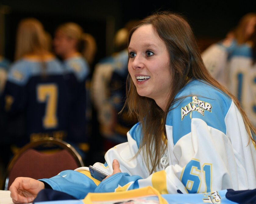 In this Saturday, Jan. 23, 2016, photo, National Women's Hockey League All-Star Kelli Stack, a forward with the Connecticut Whale, speaks with a reporter at a media event the day before the All-Star game, in Buffalo, N.Y. In just its first year, the upstart U.S.-based National Women's Hockey League beat it's longer-established, Canadian-based counterpart to the punch by paying its players this season. Now the five-team Canadian Women's Hockey League is vowing to start paying its players. The question now is whether two competing leagues are sustainable, with players and officials on both sides of the border suggesting that a merger might be best in the long run (AP Photo/Gary Wiepert)