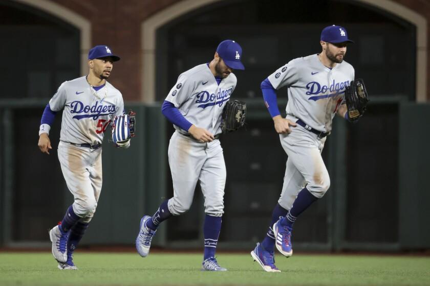 Three baseball players on a baseball field