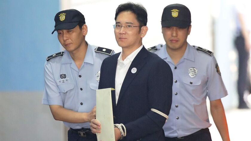 Samsung Group heir Lee Jae-yong arrives at Seoul Central District Court Friday to hear the bribery scandal verdict.