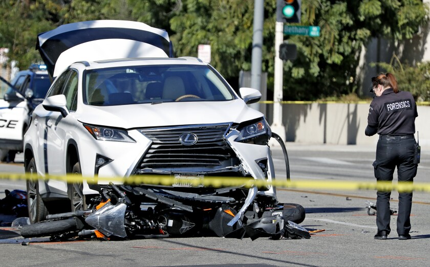 A Burbank police forensic investigator photographs the scene of a fatal collision between a vehicle and a motorcycle near the intersection of Glenoaks Boulevard and Cornell Drive on Thursday, Oct. 31, 2019.
