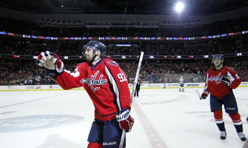 Washington Capitals center Evgeny Kuznetsov (92), from Russia, heads to the bench to celebrate his goal with left wing Andre Burakovsky, behind, from Austria, in the third period of an NHL hockey game against the Los Angeles Kings, Tuesday, Feb. 16, 2016, in Washington. The Capitals won 3-1. (AP Ph