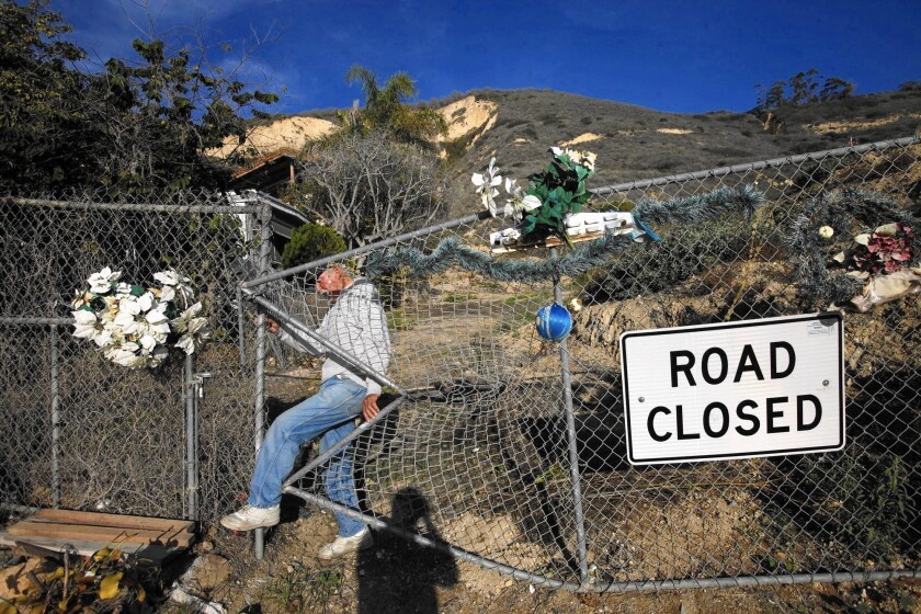La Conchita resident Ernie Garcia makes his way through a hole in a chain-link fence amid damage from the 2005 mudslide.