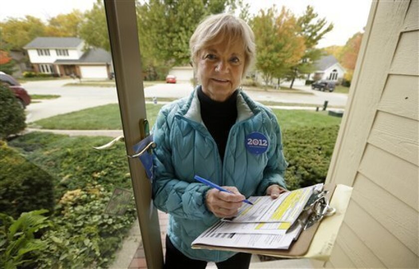 """In this photo taken Oct. 5, 2012, President Barack Obama volunteer Marilynn Wadden, of Des Moines, Iowa, stands outside her home in Des Moines. Wadden rang more than a dozen doorbells in her first hour canvassing a tidy neighborhood before stopping to take stock of her progress. Only a handful of voters were home, and, of them, only one agreed to have a ballot mailed to him so he can vote early. """"I wouldn't do this for pay. It'd be too discouraging,"""" said the 70-year-old retired principal. (AP Photo/Charlie Neibergall)"""