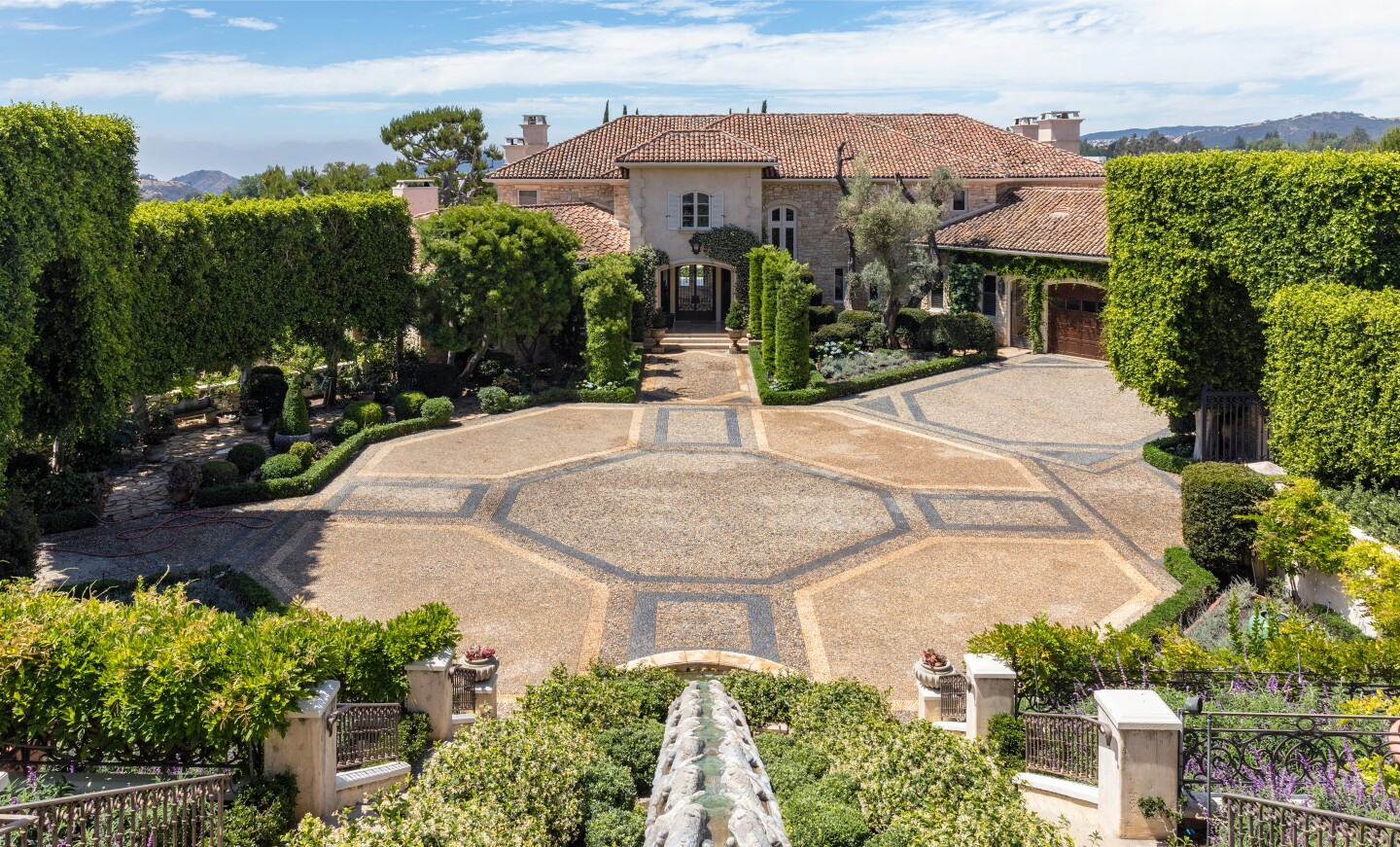 The French-inspired compound includes a dramatic main house, two guesthouses, a swimming pool, cabana and tennis court across five acres.