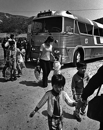 Vietnamese children dressed in new but mismatched clothes file off a Greyhound charter bus with their families at Camp Pendleton. They were first evacuated to Guam and then to Pendleton. Tens of thousands of South Vietnamese were brought here after the communist takeover and housed in big squad tents while sponsors were lined up to help them resettle in the U.S. See full story