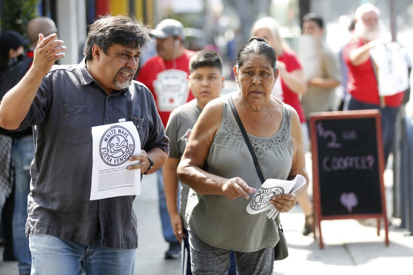 "Leonardo Vilchis, left, hands out fliers against Weird Wave Coffee in Boyle Heights in June. ""There"