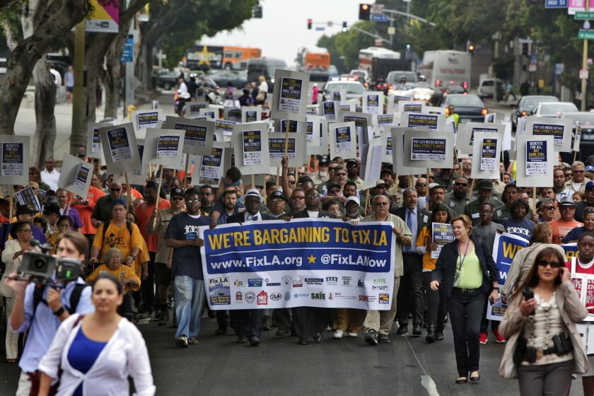 """Hundreds of city workers march on 1st Street on their way to Los Angeles City Hall on Tuesday morning, protesting """"predatory fees"""" the city pays to Wall Street banks."""