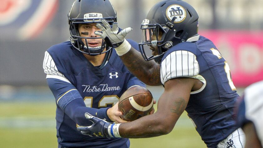 Notre Dame quarterback Ian Book (12) hands off to running back Dexter Williams (2) during the first