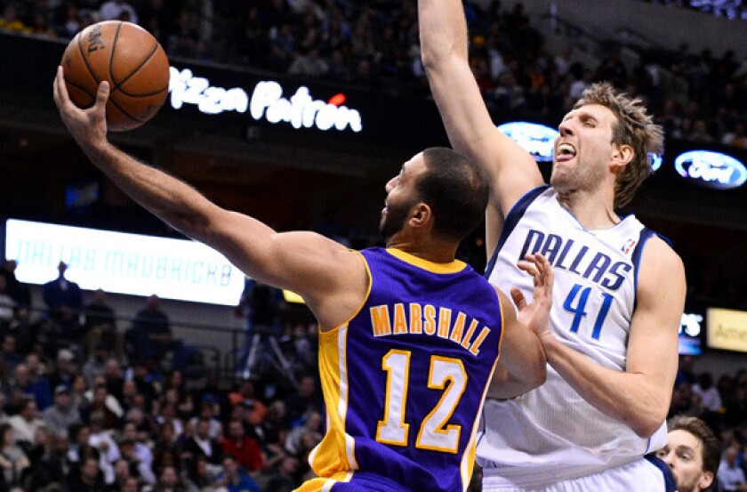 Lakers point guard Kendall Marshall puts up a shot against Dallas Mavericks forward Dirk Nowitzki during the second half of the Lakers' 110-97 road loss Tuesday.