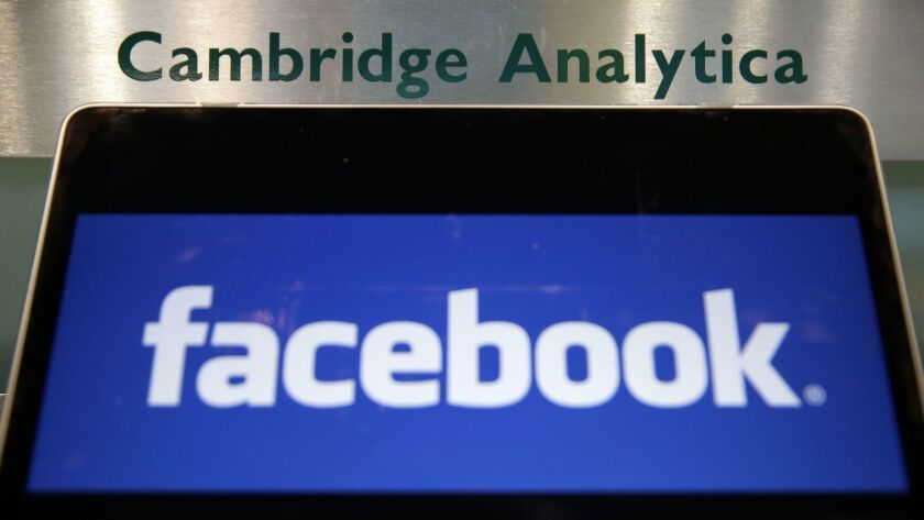 A laptop showing the Facebook logo is held alongside a Cambridge Analytica sign at the entrance to the building housing the offices of Cambridge Analytica in London.