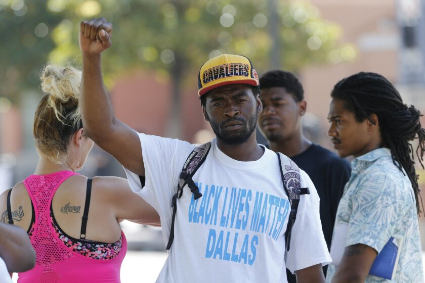 In this Friday, July 8, 2016 photo, Marcus Carter raises his fist toward news media as he waits for a commuter rail near the scene where a gunman opened fire on Dallas police officers the night before, in Dallas. Carter was waiting for his girlfriend and watching the protest Thursday evening when h