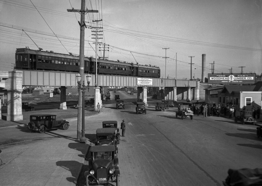 Pacific Electric Red Car stopped on Pico Street viaduct with people and autos below.