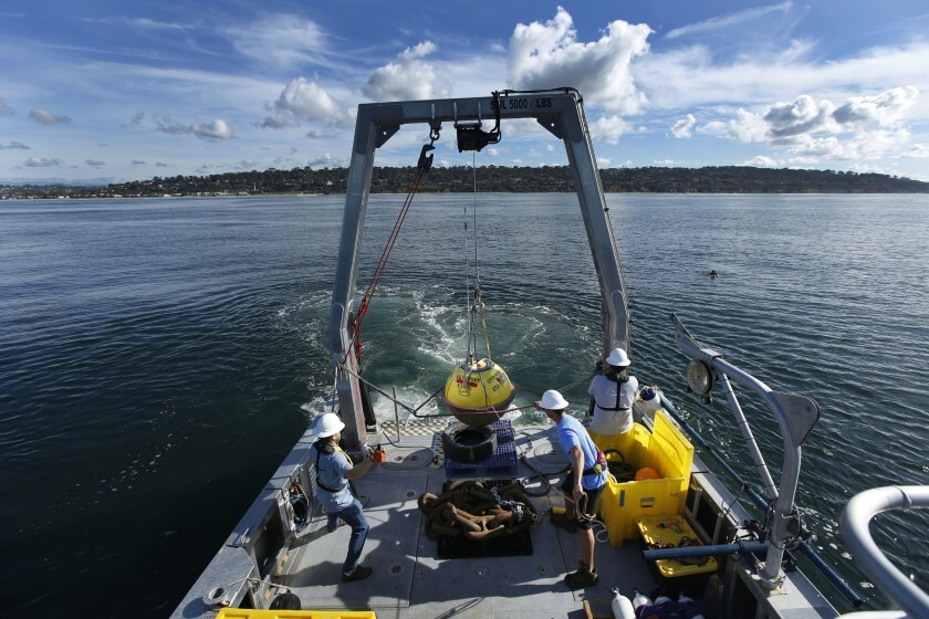 Andrew Gray, left, Les Hanson, and Victor Aguilar of UC San Diego's Coastal Data Information Program hoist a wave buoy into the ocean off the coast of Del Mar on Dec. 5, 2019. The buoy measures wave heights and current patterns near the area where bluffs have collapsed.