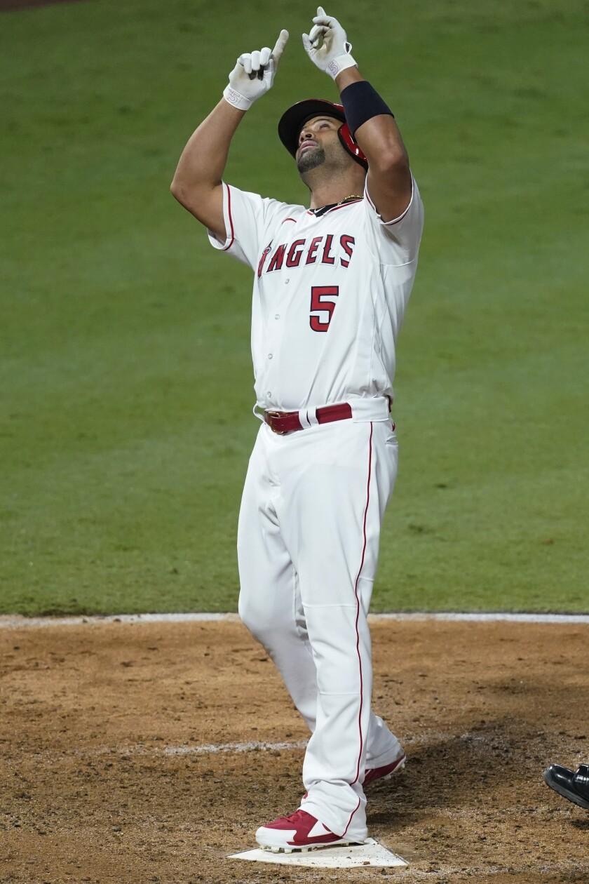 El dominicano Albert Pujols, de los Angelinos de Los Ángeles, apunta al cielo tras conectar un jonrón en el séptimo inning del duelo del viernes 18 de septiembre de 2020, ante los Rangers de Texas (AP Foto/Ashley Landis)