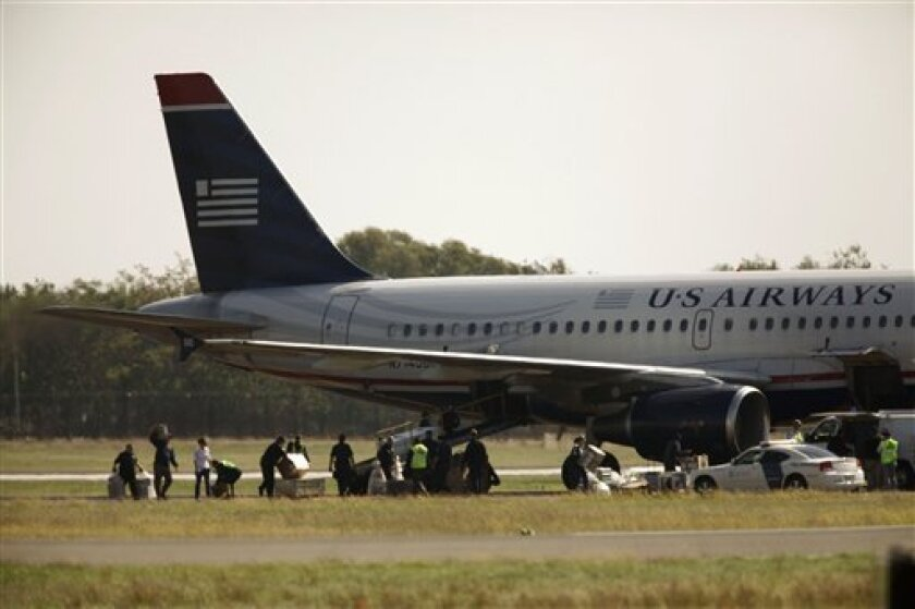 Authorities move items near a plane on a closed runway at Philadelphia International Airport in Philadelphia, Thursday, Oct. 7, 2010. Transportation security officials removed passengers from the Bermuda-bound flight Thursday after reports that someone was helping to load the plane without a security badge. (AP Photo/Matt Rourke)