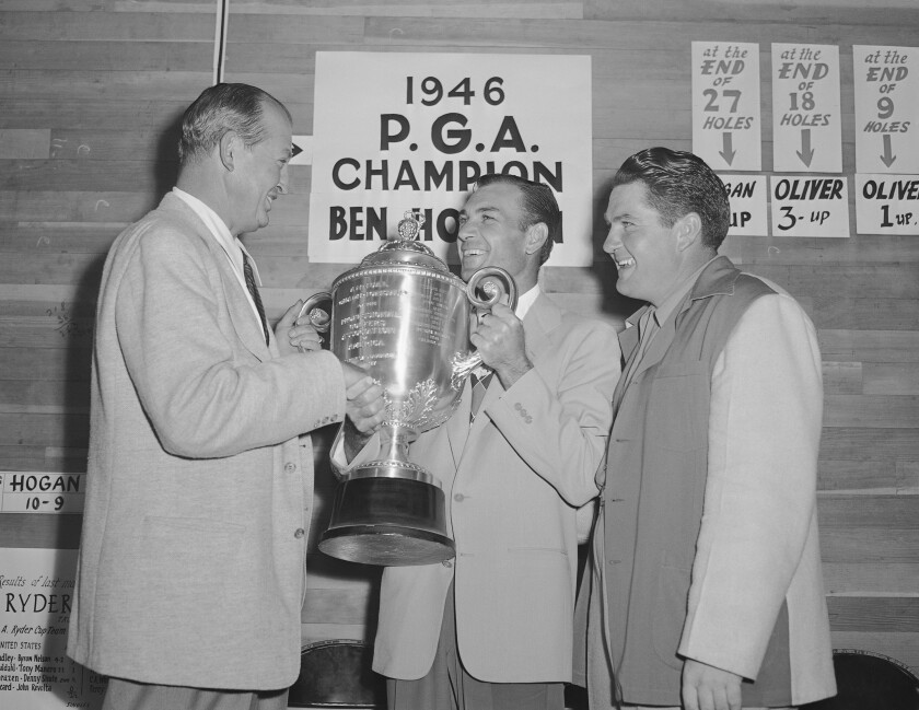 FILE - Ben Hogan gets the PGA Championship trophy from PGA president Ed Dudley, left, after winning the golf tournament in Portland, Oregon, in this Aug. 25, 1946, file photo. Hogan beat Ed Oliver, right, 6 and 4. It was 75 years ago when Ben Hogan won the first of his nine majors at the 1946 PGA Championship.(AP Photo/Paul Wagner, File)