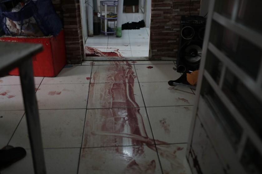 Una mancha de sangre cubre el piso de una casa luego de un operativo de la policía en la favela de Jacarezinho, en Río de Janeiro, el jueves 6 de mayo de 2021. (AP Foto/Silvia Izquierdo)