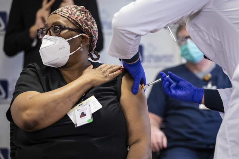 Barbara Shields-Johnson, director of Nursing Services at Loretto Hospital, gets her second and final dose of the Pfizer-BioNTech COVID-19 vaccine at Norwegian American Hospital on the West Side, Tuesday morning, Jan. 5, 2021. (Ashlee Rezin Garcia/Chicago Sun-Times via AP)