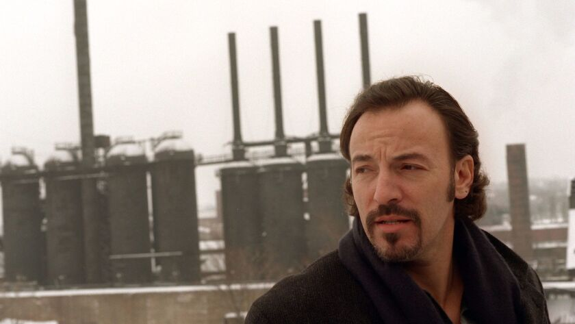 """Springsteen stands in front of the """"Jenny,"""" a shut down steel furnace in Youngstown, Ohio, on Jan. 13, 1996."""