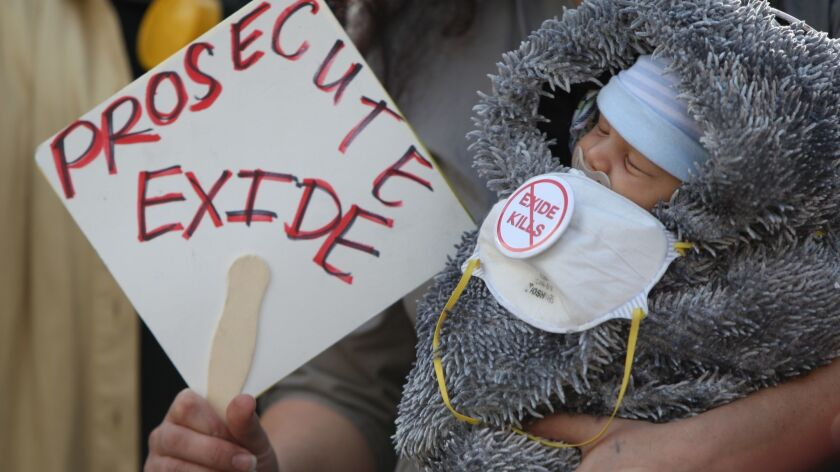 A resident of Boyle Heights holds her 1-month-old son during a 2014 protest in downtown Los Angeles against the Exide battery plant.