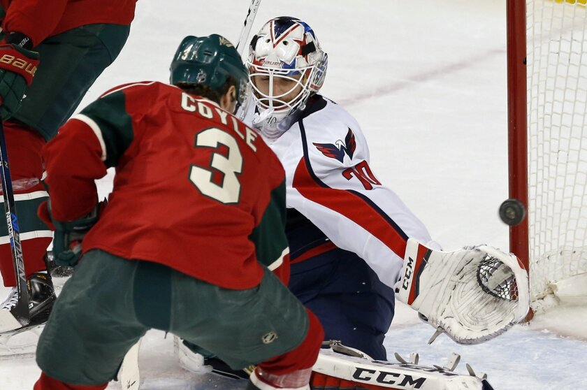 Washington Capitals goalie Braden Holtby, right, stops a shot by Minnesota Wild's Charlie Coyle in the first period of an NHL hockey game, Thursday, Feb. 11, 2016, in St. Paul, Minn. (AP Photo/Jim Mone)