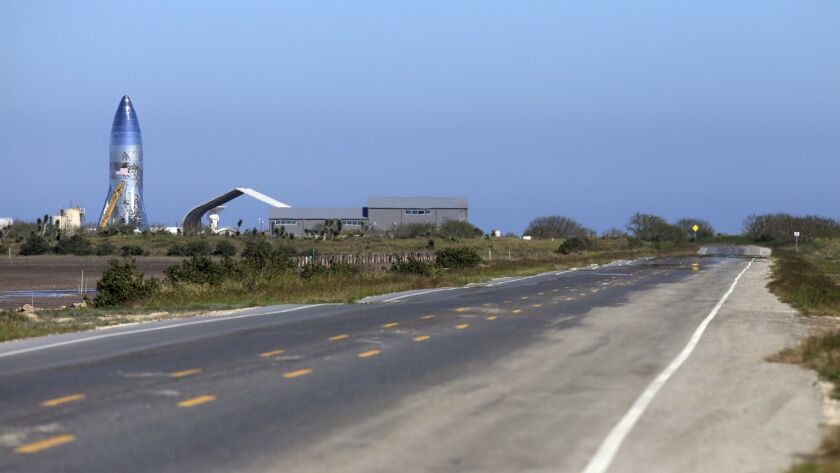 In this Saturday, Jan. 12, 2019 photo, a SpaceX prototype Starship hopper, left, rises at Boca Chica
