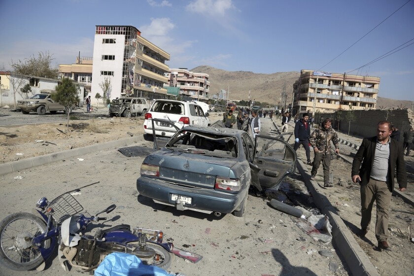 Afghan security personnel gather at the site of a car bomb attack in Kabul on Nov. 13, 2019.