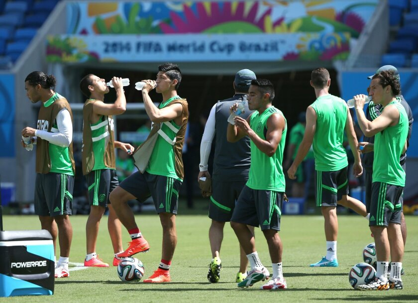 Mexico's soccer players drink water at a training session for the World Cup at the Arena das Dunas stadium in Natal, Brazil, Thursday, June 12, 2014. (AP Photo/Sergei Grits)