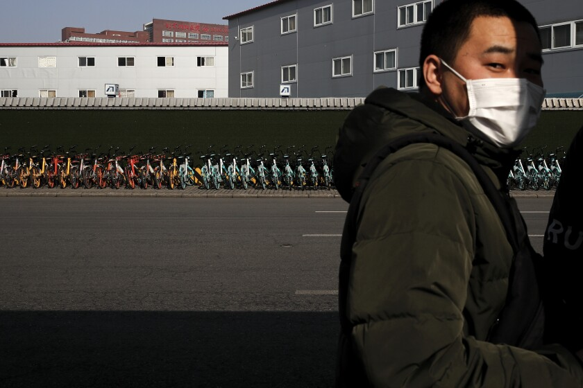 A man wearing a mask stands near a pile of bicycles from bike-sharing companies parked outside a subway station in Beijing, Monday, Feb. 10, 2020. China reported a rise in new virus cases on Monday, possibly denting optimism that its disease control measures like isolating major cities might be working, while Japan reported dozens of new cases aboard a quarantined cruise ship. (AP Photo/Andy Wong)