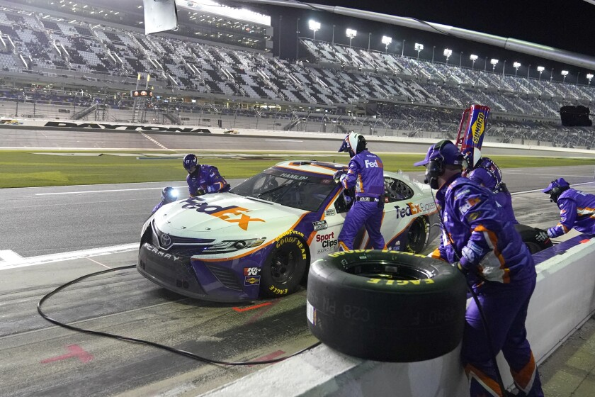 Denny Hamlin's crew changes tires and adds fuel during a pit stop in the 2021 NASCAR Clash at Daytona International Speedway.