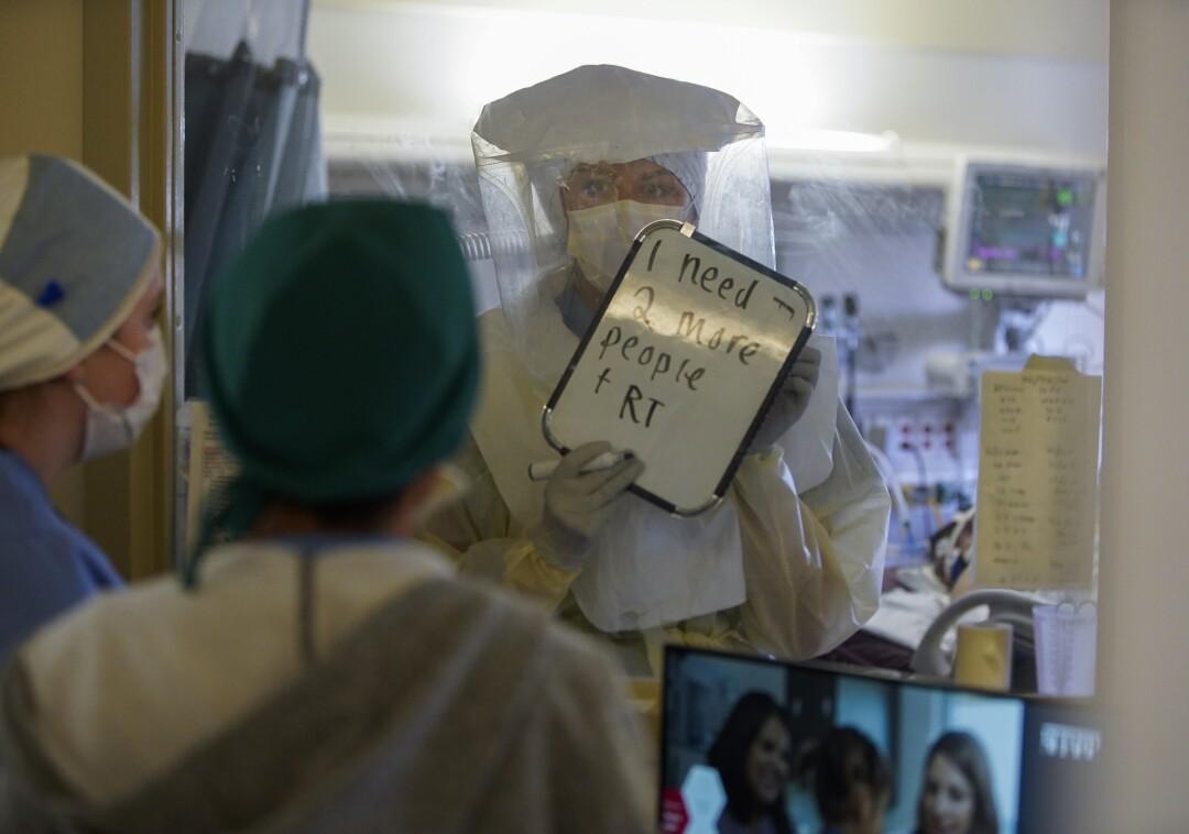 Jessica Osburn, enfermera registrada en el Centro Médico Sharp Chula Vista, revisa a un paciente con covid 19.