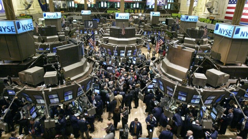 ** FILE ** In a file photo traders move between stations on the floor of the New York Stock Exchange