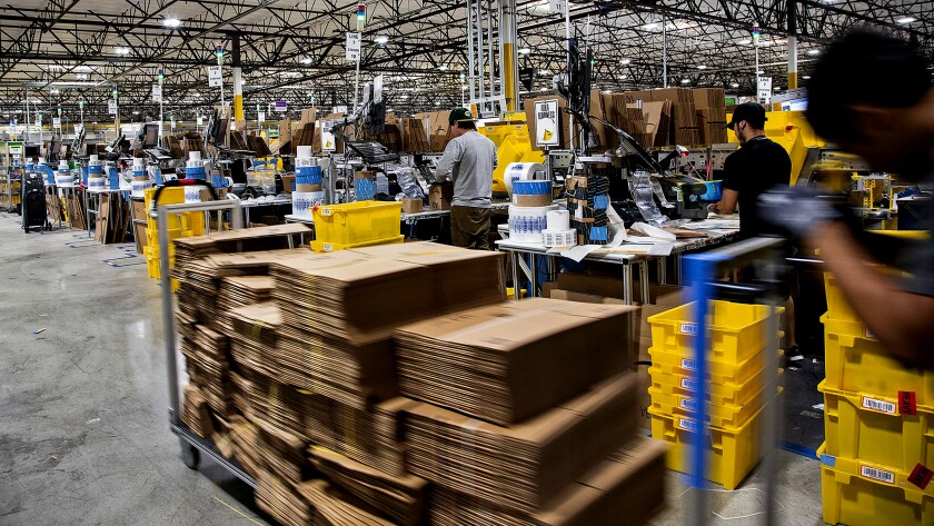 Workers quickly pack items on Cyber Monday at the Amazon Fulfill
