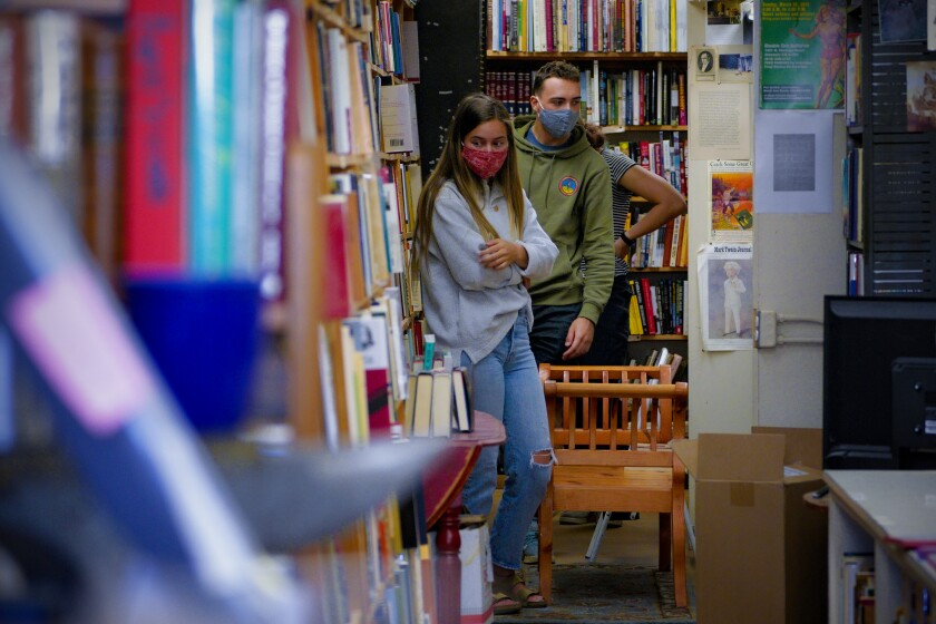 Hannah Park (left), Zander Gore and Bella Gore browse the selection of Maxwell's House of Books in La Mesa.