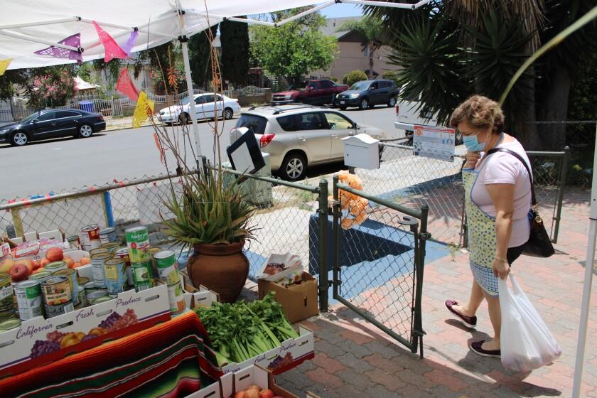 María Salgado surte su despensa en una de las cuatro Mesas de Esperanza, esta instalada en Barrio Logan