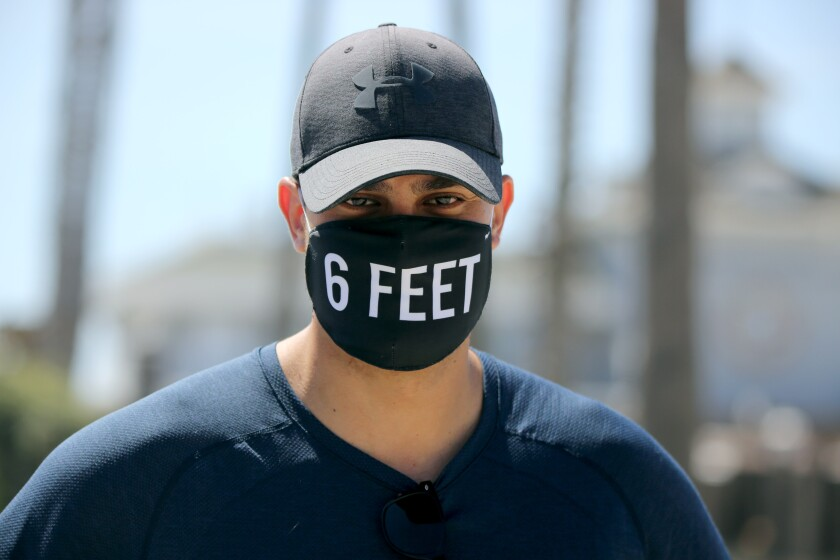 """A man wears a black face mask that says """"6 feet"""" on it."""