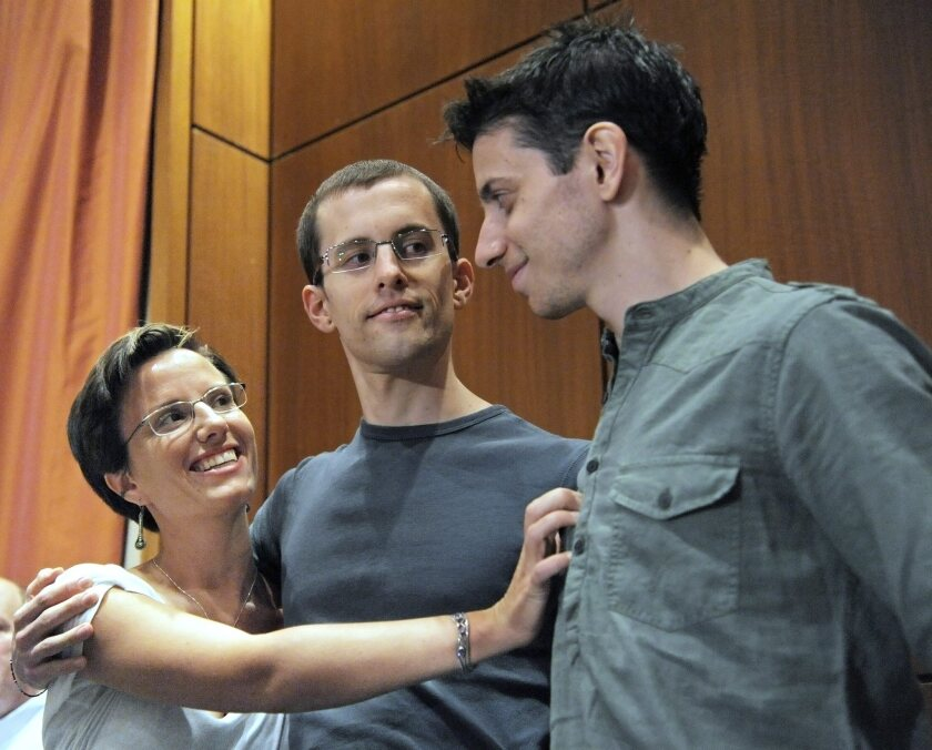 Released U.S. hikers Shane Bauer, center, and Josh Fattal, right, are embraced by fellow hiker Sarah Shourd after a press conference in New York. Bauer and Fattal were jailed in Iran and finally freed on Sept. 21, 2011 after almost 26 months. Shourd was jailed in an Iranian prison for 410 days.