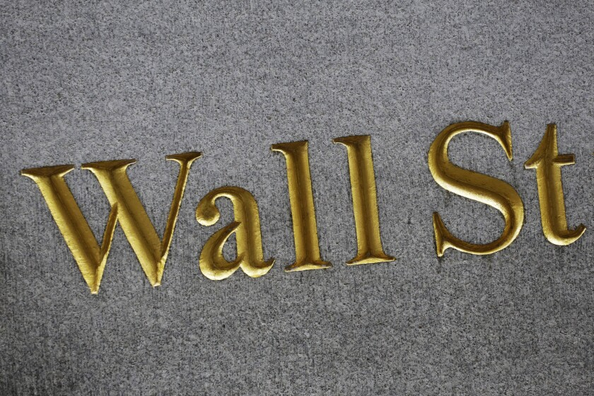 A sign for Wall Street is carved into the side of a building in New York.