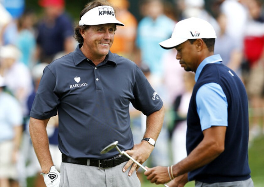 Phil Mickelson was all smiles after making a birdie at No. 11 while playing partner Tiger Woods was