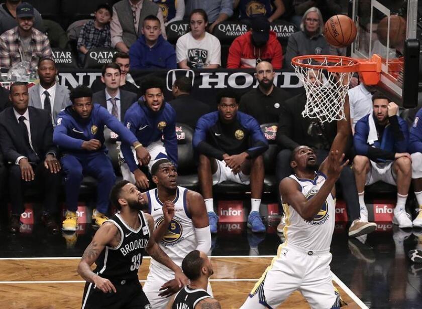 El alero de los Golden State Warriors, Kevin Durant (R), derrota a los defensores de los Nets en la primera mitad de su partido de baloncesto de la NBA en el Barclays Center en Brooklyn, Nueva York, EE. UU., 28 de octubre de 2018. (Baloncesto, Estados Unidos, Nueva York). EFE