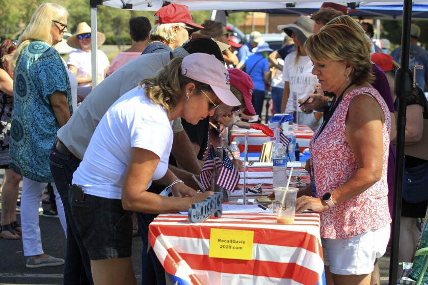 Susan Lee signs petitions to recall Gov. Gavin Newsom and to allow worship inside churches at an Aug. 15 rally in Carlsbad.