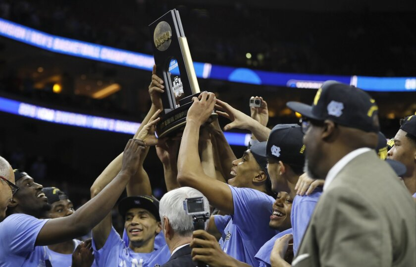 North Carolina players celebrate with the trophy after winning a regional final men's college basketball game against Notre Dame in the NCAA Tournament, Sunday, March 27, 2016, in Philadelphia. North Carolina won 88-74 to advance to the Final Four. (AP Photo/Chris Szagola)