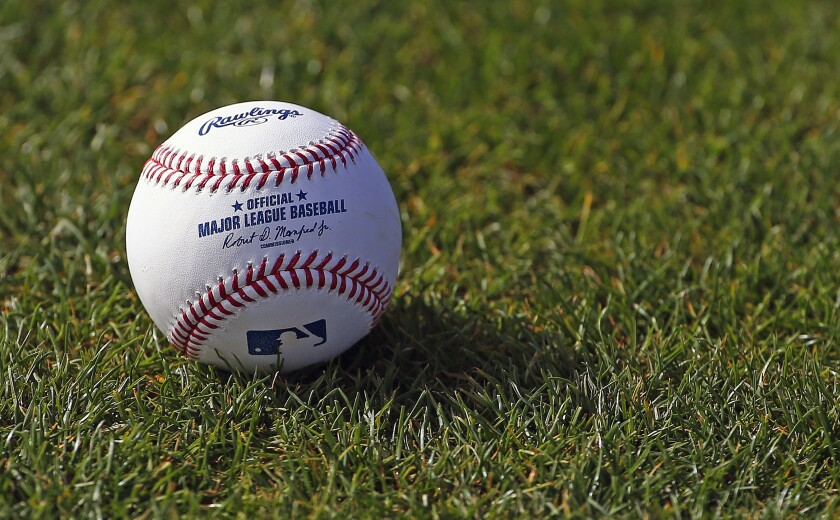 A baseball is shown on the grass at the Cincinnati Reds' spring training facility in Goodyear, Ariz.