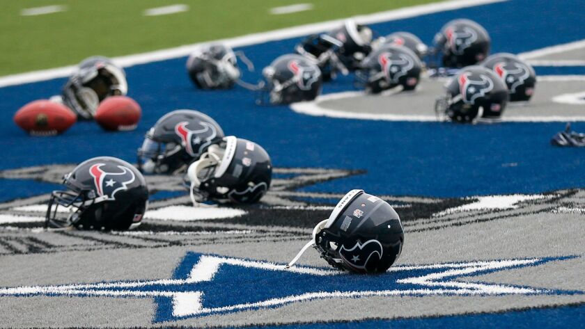 Several Houston Texans helmets sit over the Dallas Cowboys logo in the end zone as the Texans prepar