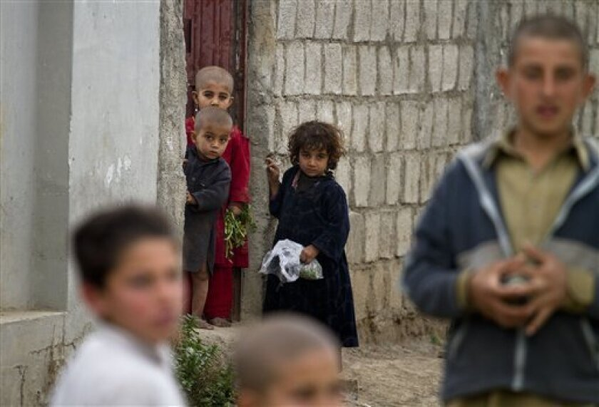 In this photo taken Thursday, March 8, 2012,   Afghan refugee children gather in the neighborhood next to a house in Haripur, Pakistan, that Pakistan's intelligence agency believes Osama bin Laden lived in for nearly a year until he moved into the villa where he was eventually killed.  The home in