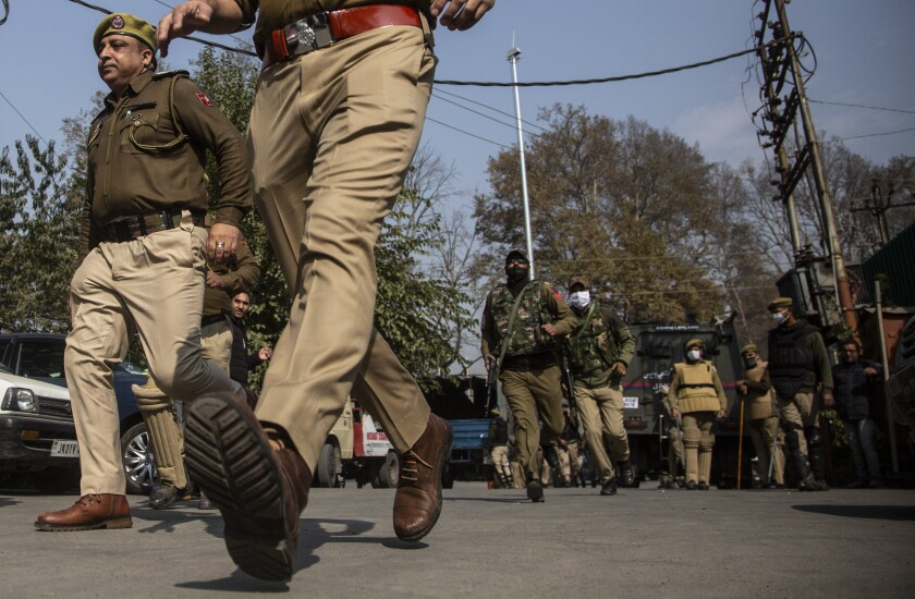 Indian police chase activists of Peoples Democratic party (PDP) protesting against India's new land laws that allows any Indian citizen to buy land in the disputed region in Srinagar, Indian controlled Kashmir, Thursday, Oct. 29, 2020. Until last year, Indians were not allowed to buy property in the region. But in August 2019, Prime Minister Narendra Modi's government scrapped the disputed region's special status, annulled its separate constitution, split the region into two federal territories. (AP Photo/Mukhtar Khan)