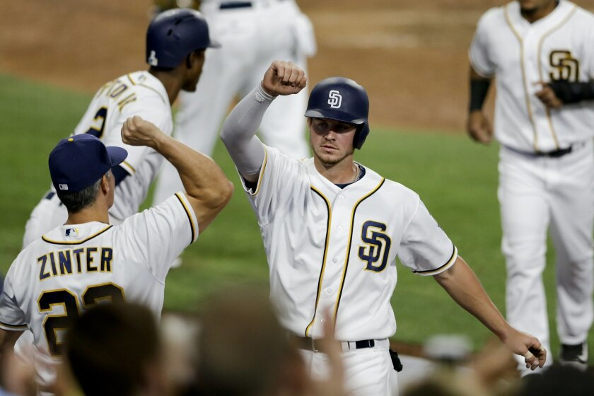 San Diego Padres' Wil Myers, center, is greeted by hitting coach Alan Zinter after hitting a two-run home run during the fourth inning of a baseball game against the Pittsburgh Pirates on Tuesday, April 19, 2016, in San Diego. (AP Photo/Gregory Bull)