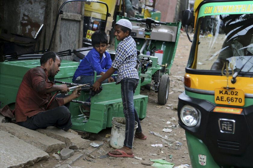 An Indian worker is helped by children to make a chassis for a three-wheeled vehicle at an industrial unit in Bangalore, India, Tuesday, May 31, 2016. India says its economy grew 7.6 percent in the financial year that ended March 31 and a swift 7.9 percent in the last quarter of the year keeping it